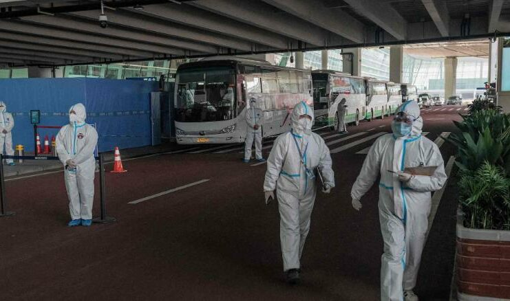 Health workers stand next to buses at a cordoned-off section